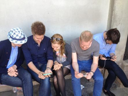 Fans of the Swedish royals watch the baptism on their mobile phones outside the Royal Palace
