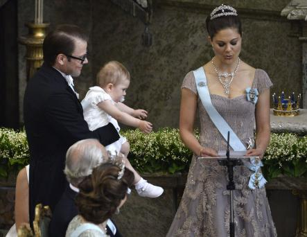 Prince Daniel holds on to Estelle as mother Crown Princess Victoria reads during the ceremonyPhoto: Scanpix