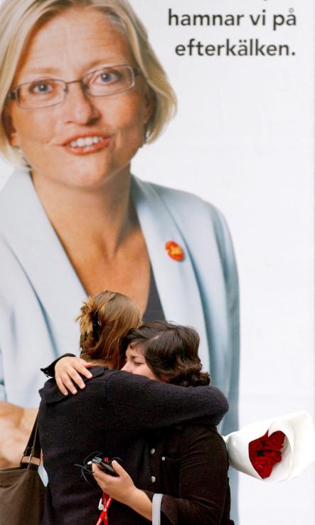 Two women embrace in front of a billboard featuring Lindh in downtown Stockholm, on the day Lindh died, after she was stabbed by a man in the NK department store in central Stockholm.Photo: Dusan Vranic/Scanpix
