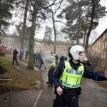 Police herd Swedish neo-Nazis past apartments blcok in Kärrtorp, Stockholm on Sunday December 15th, 2013 after an anti-racism protest was attacked.