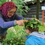 A woman in traditional dress places a Midsummer crown on a child's head.Photo: The Local/Solveig Rundquist