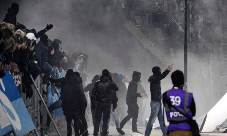 Fans throw flares and enter pitch in Swedish football riot