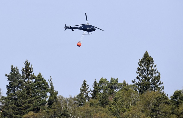 Helicopters water bomb wildfire outside Stockholm